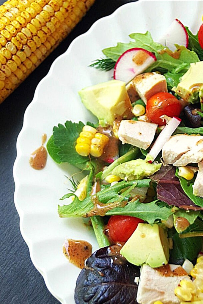 Roasted Corn Salad Recipe on white plate with roasted corn next to it