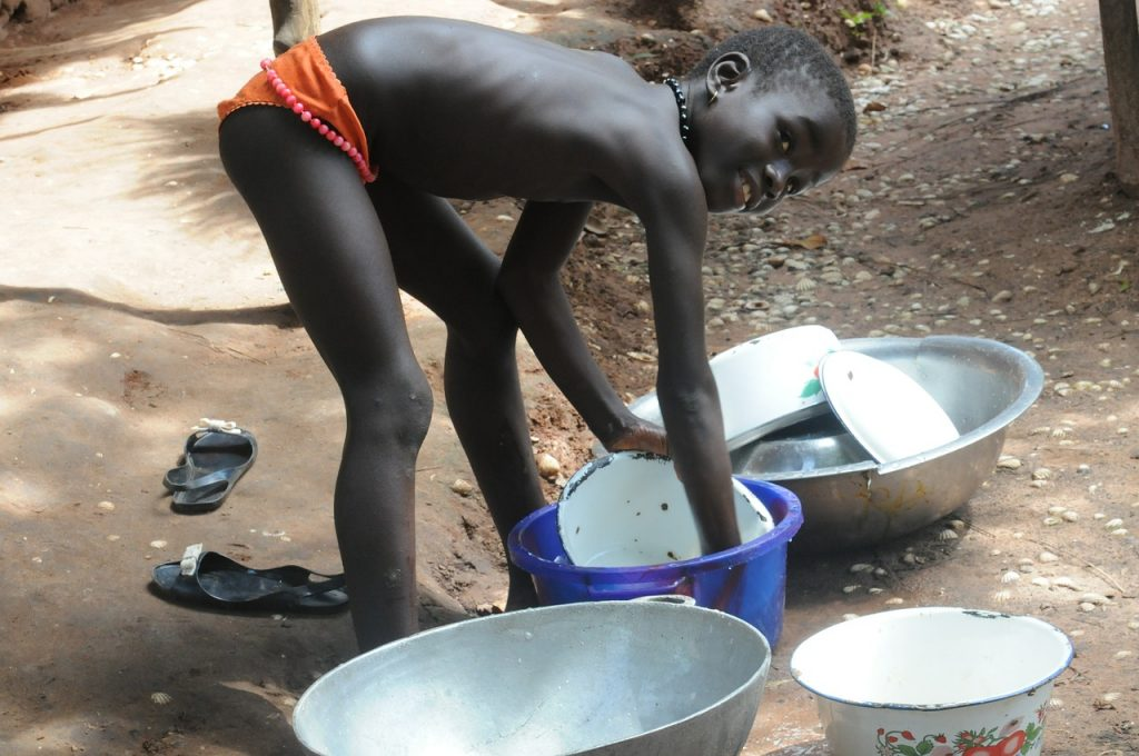small child in poor country washing dishes in outdoor tubs
