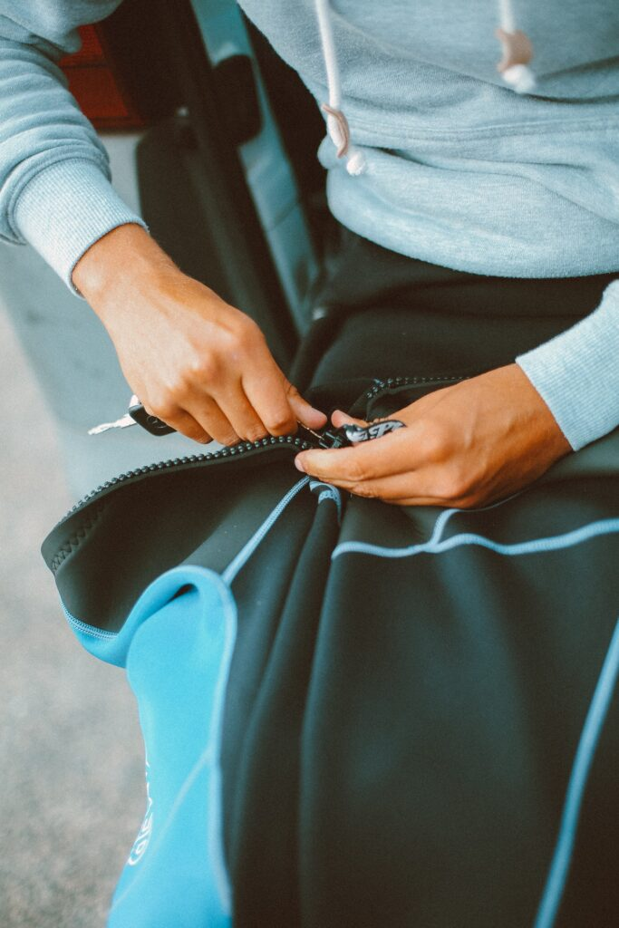 person holding the zipper portion of a jacket in their lap to represent fixing a broken zipper