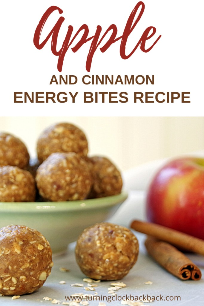 Apple and cinnamon energy bites in a small bowl with fresh apple and cinnamon stick