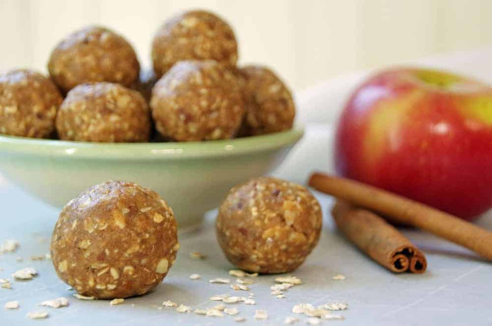 bowl of no bake apple crisp energy bites near fresh apple and cinnamon stick and raw oats