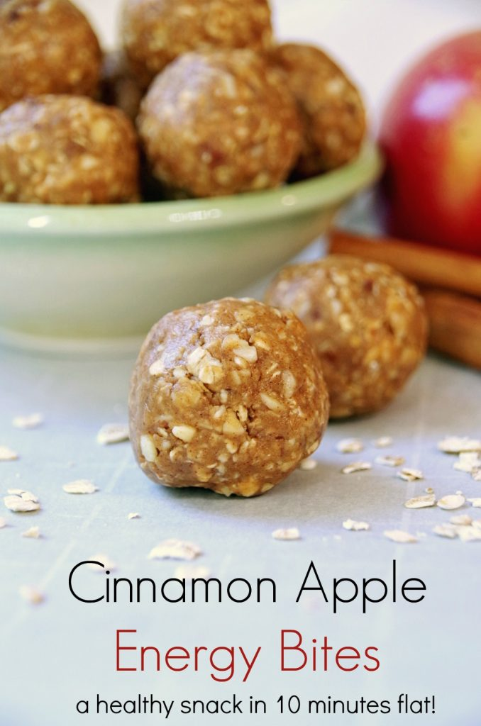 Cinnamon Apple Energy Bites in small bowl on white surface scattered with dried oatmeal