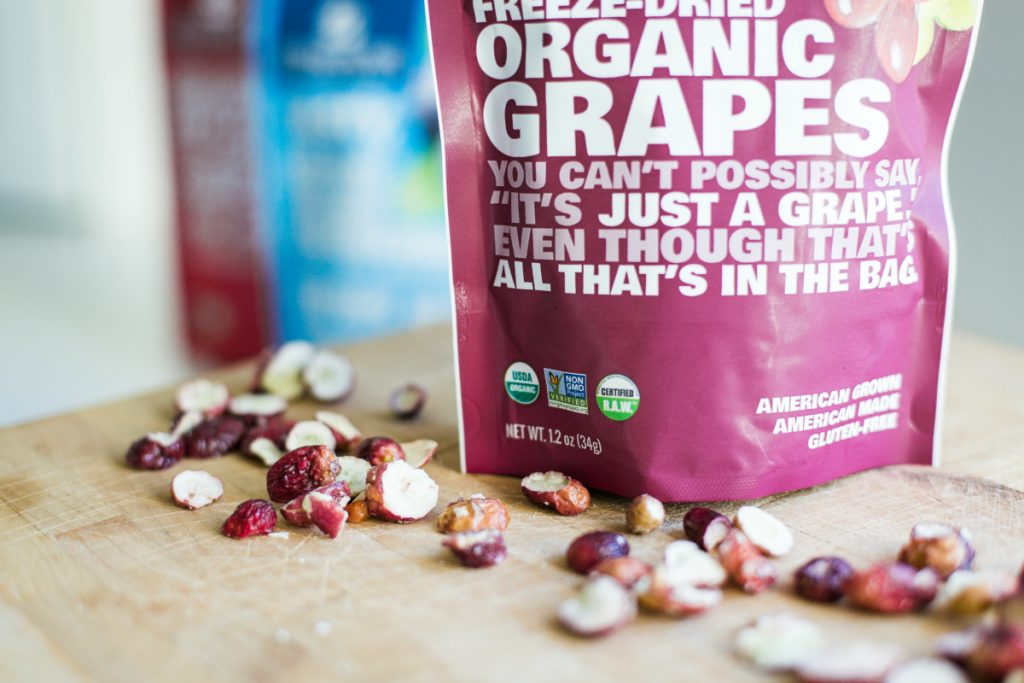 package of freeze dried grapes on cutting board
