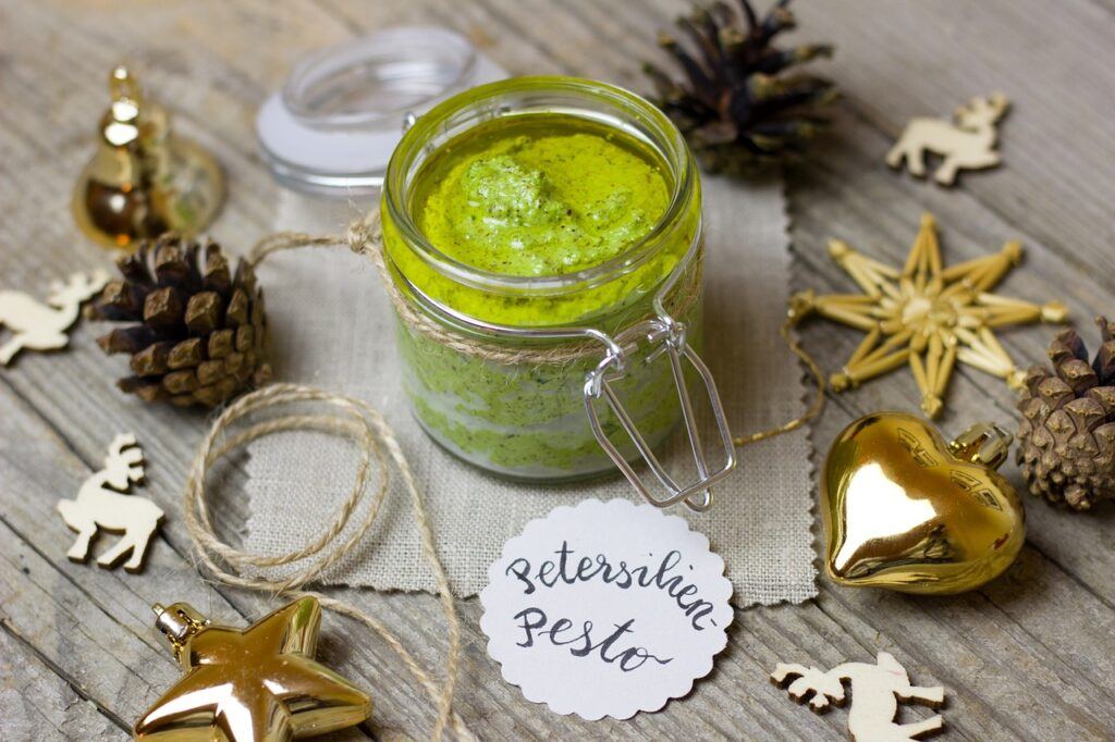 pesto as a homemade Christmas gift with holiday decorations around it.