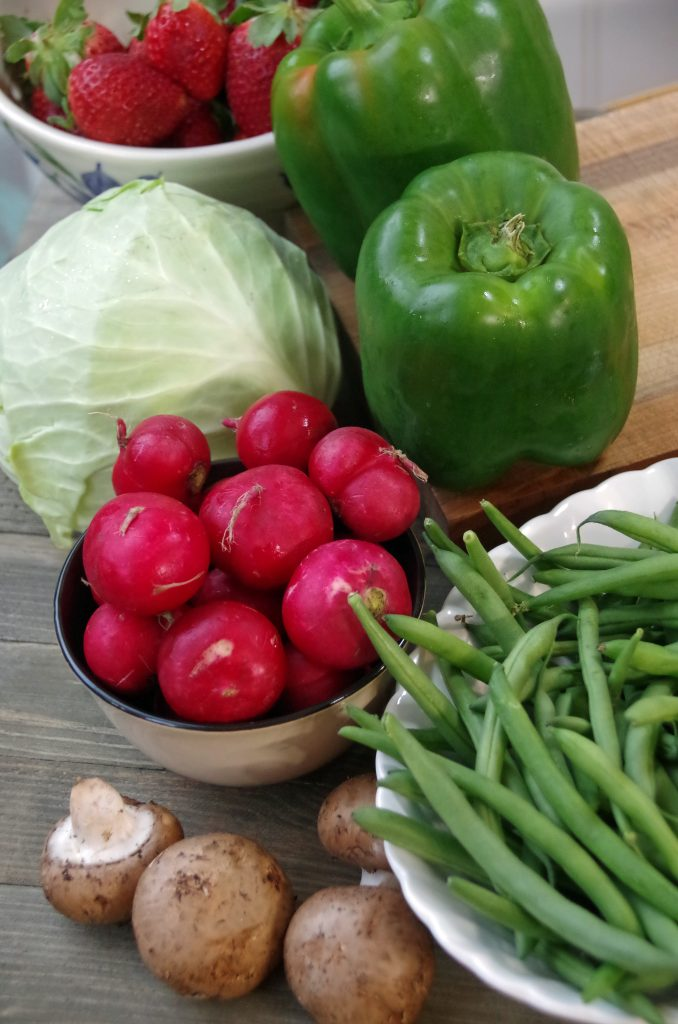 organic food on a cutting board including radishes, mushrooms, peppers, cabbage green beans and strawberries