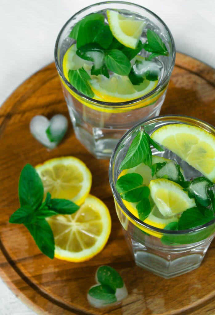 glasses of lemon balm and lemons in water