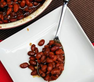 New England Style Homemade Baked Beans from Scratch in a ceramic pot with metal spoon
