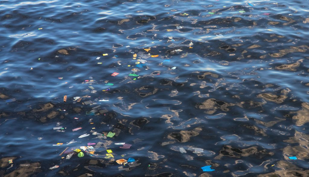 Garbage in sea water. Plastic trash in ocean. Ecological problem. Urban seaside pollution