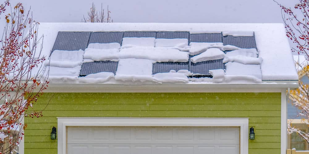Solar panels on snow covered roof in winter.