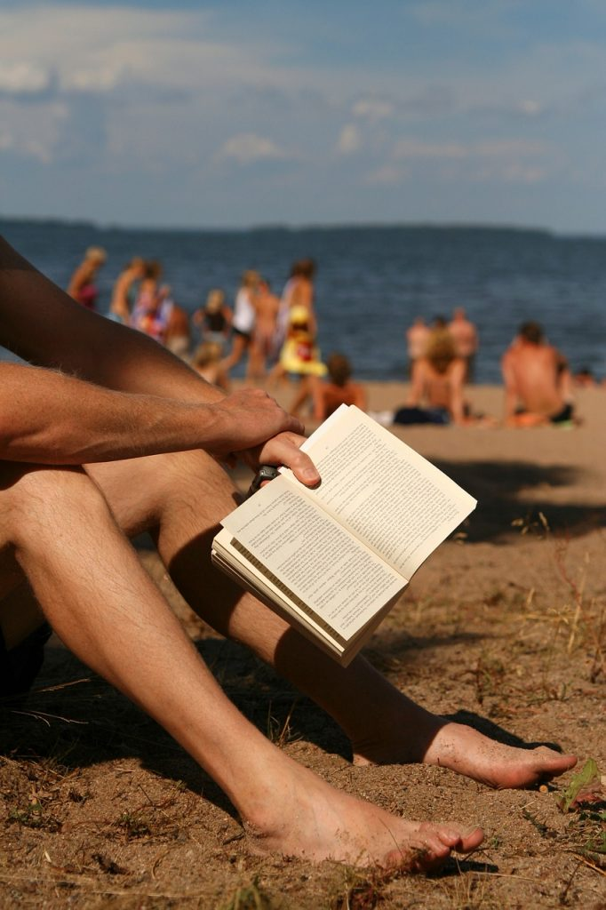 man relaxing on beach with book