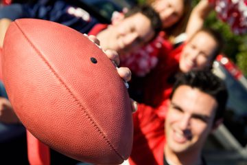 Tailgating: Man Holds Football Out To Camera