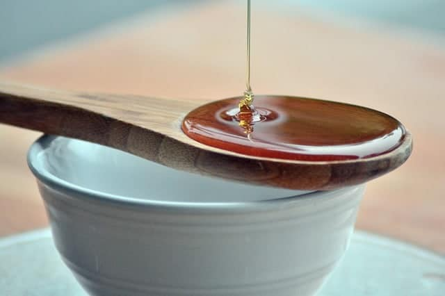 honey on a wooden spoon with bowl