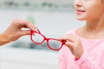 health care, people, eyesight and vision concept - close up of optician giving glasses to little girl at optics store