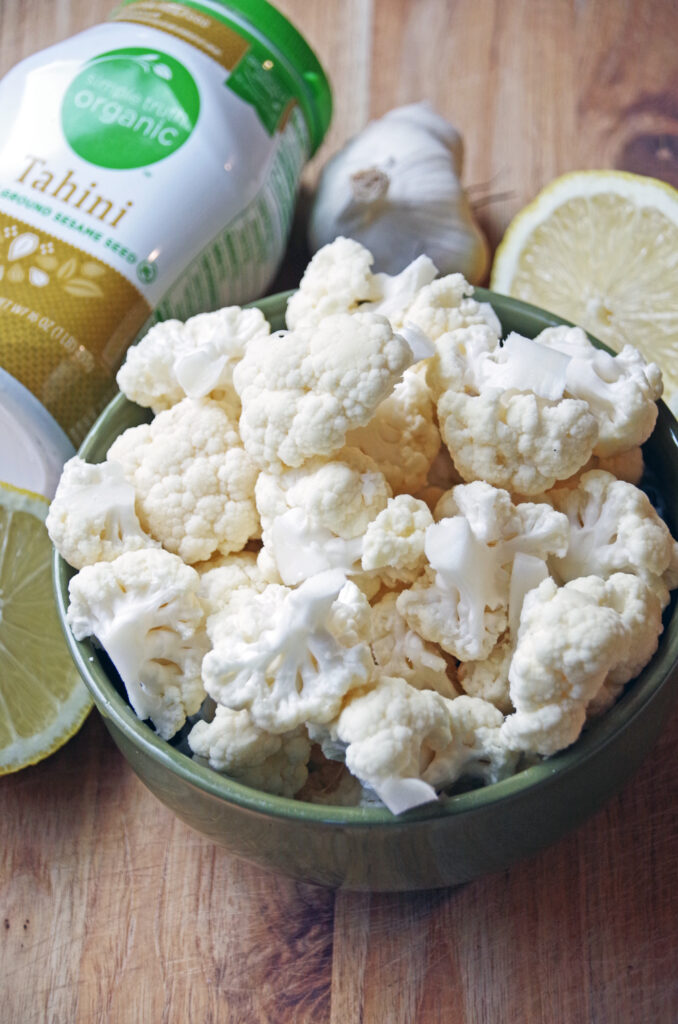 bowl of fresh cauliflower on a cutting board with lemon, garlic and tahini