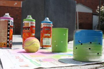 old tin cans and spray paint on newspaper for crafting