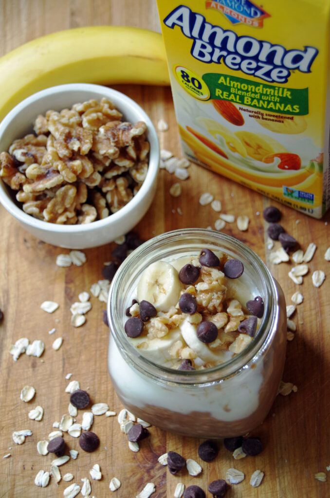 mason jar with chocolate oatmeal and container of walnuts and jug of almond breeze banana almond milk