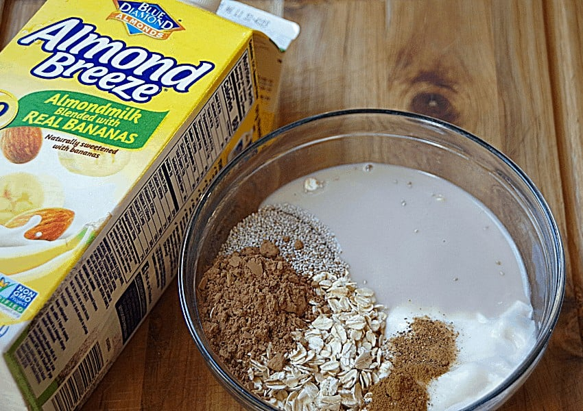 oatmeal ingredients in glass bowl and banana almond milk on cutting board