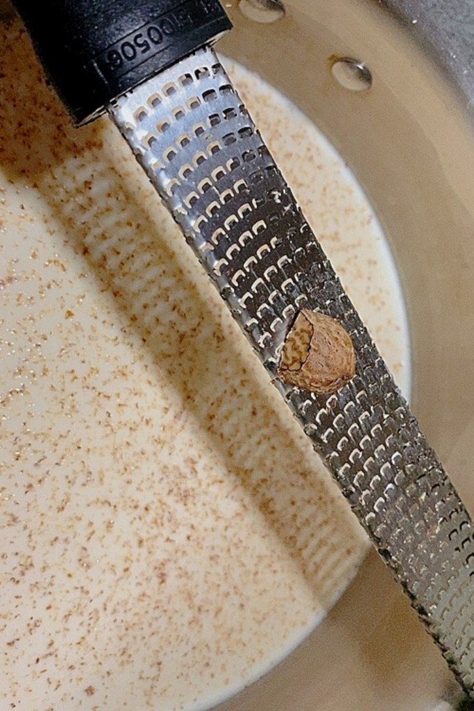 Grating nutmeg into milk for homemade eggnog