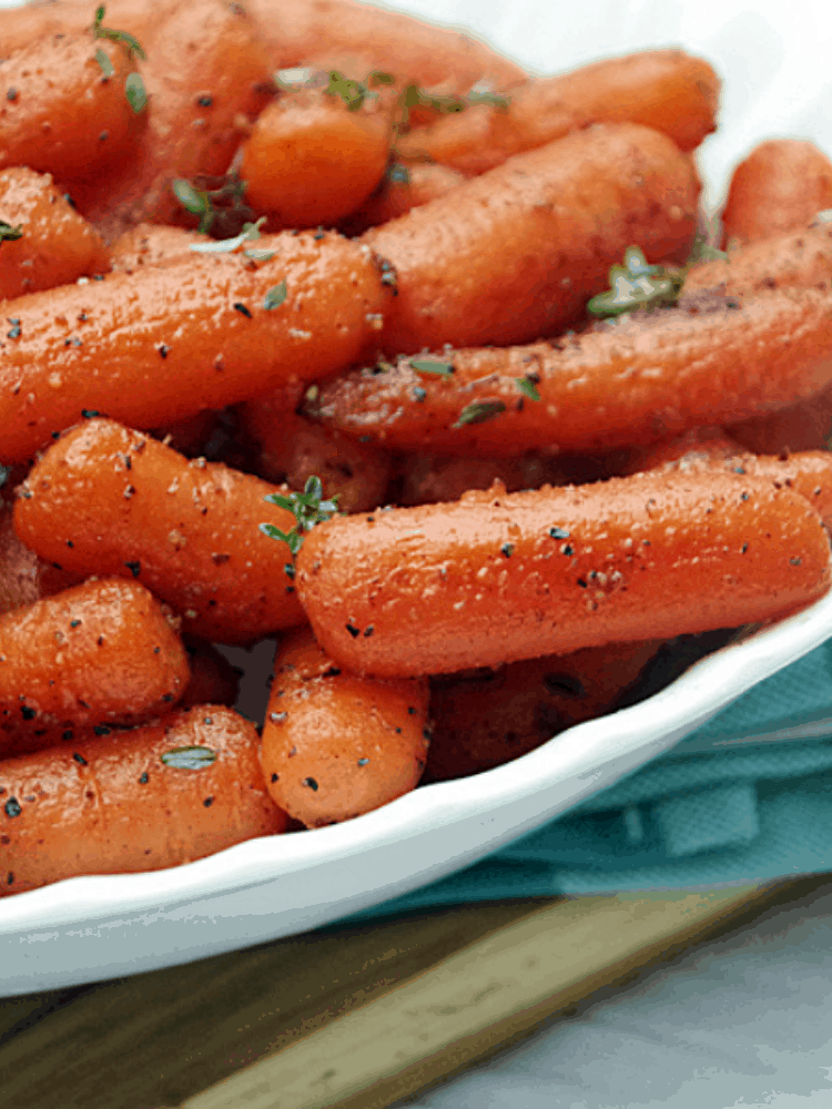 roasted carrots with fresh herbs in a white bowl