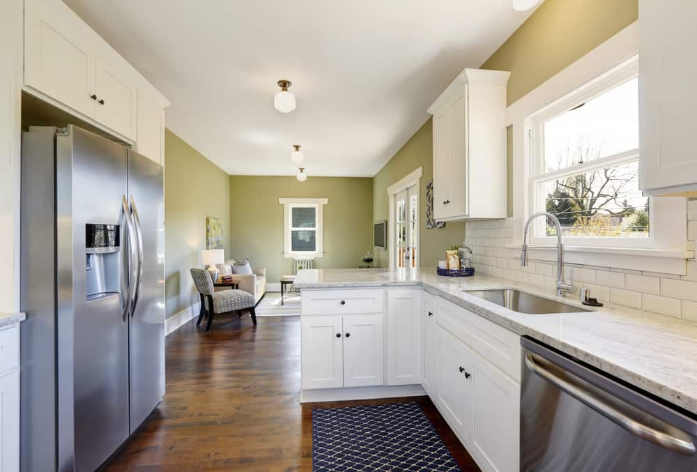 Freshly updated white and green kitchen room with custom cabinets, granite counters, new stainless appliances and a breakfast bar.