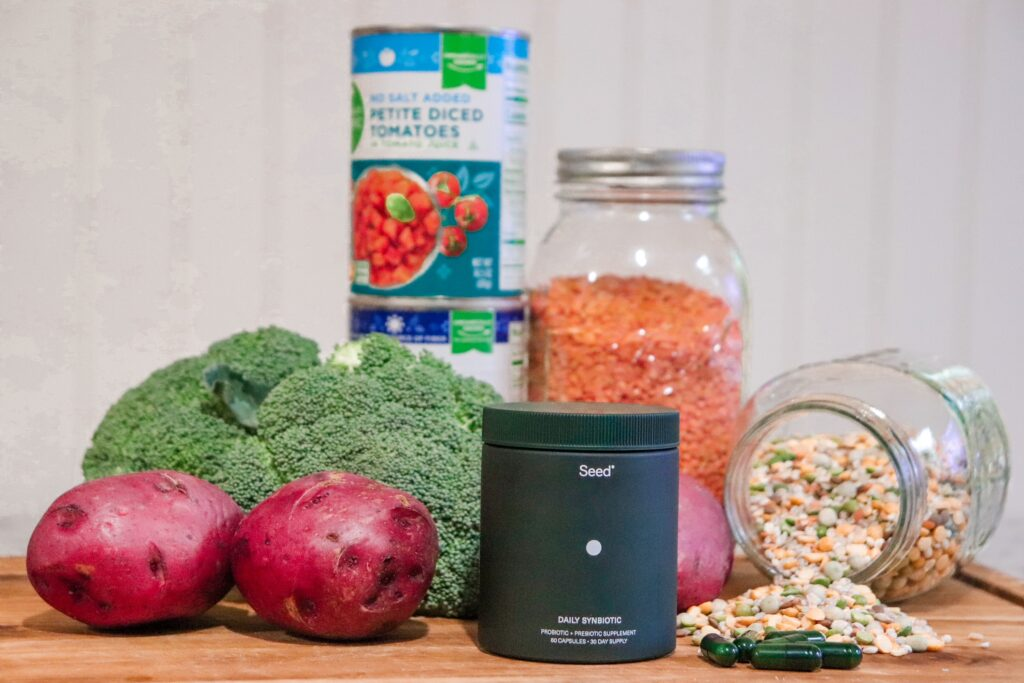 fresh vegetables and jars and cans of clean eating approved foods with seed synbiotics on a cutting board
