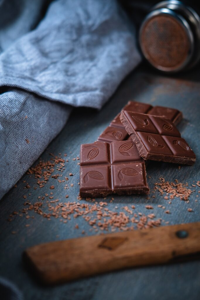 squares of chocolate and cocoa powder on cutting board with kitchen towel near it.