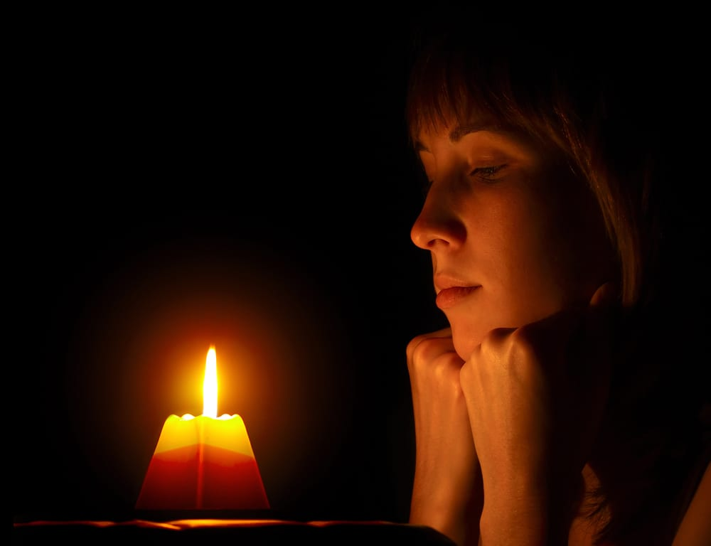 Woman sitting in front of candle in the dark for Earth Hour 2021