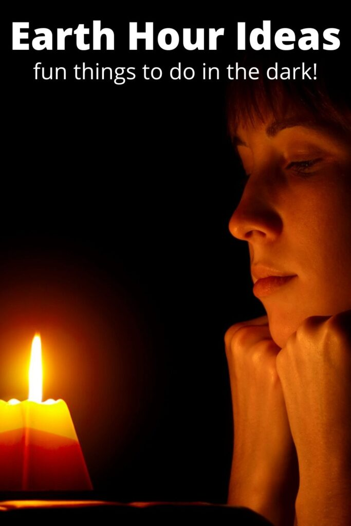 woman sitting in the dark with a candle to celebrate Earth Hour
