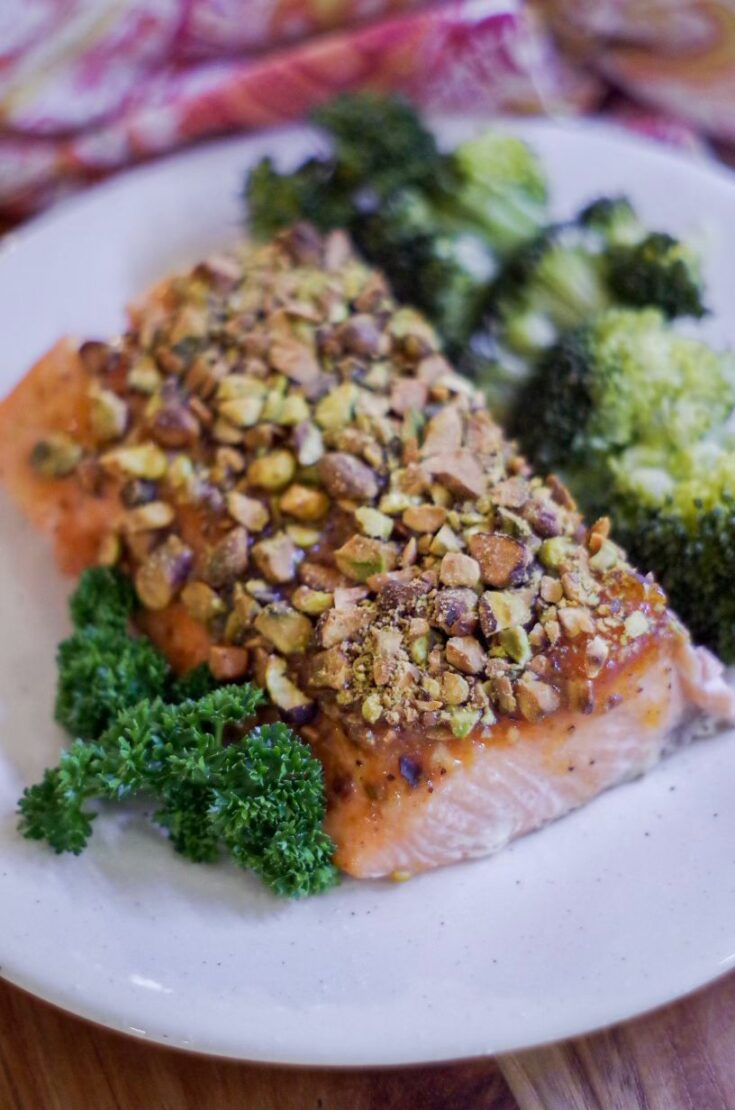 healthy pistachio salmon on a white plate with broccoli