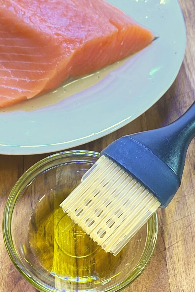 preparing salmon fillets for baking with a small bowl of olive oil and a brush