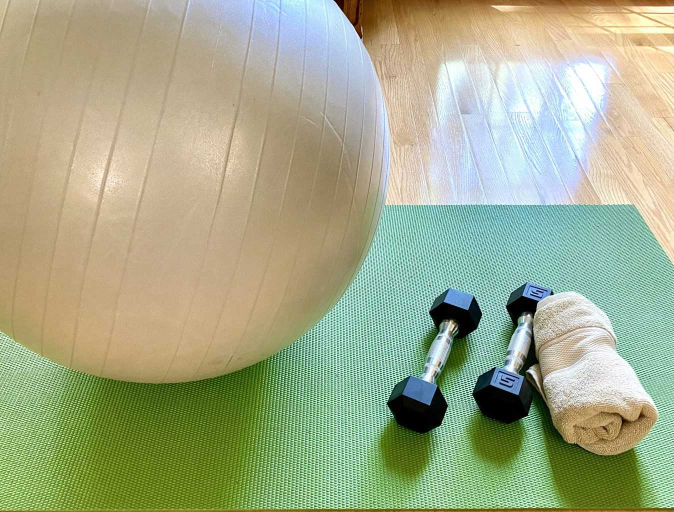 exercise ball, weights and towel on yoga mat
