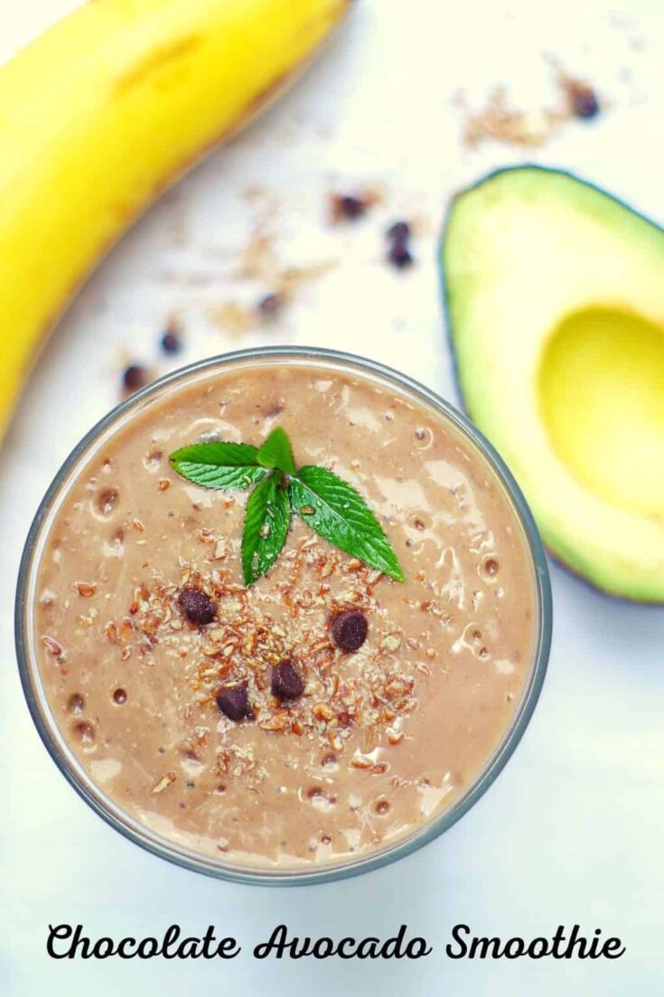 chocolate avocado smoothie in a glass with banana and avocado next to it