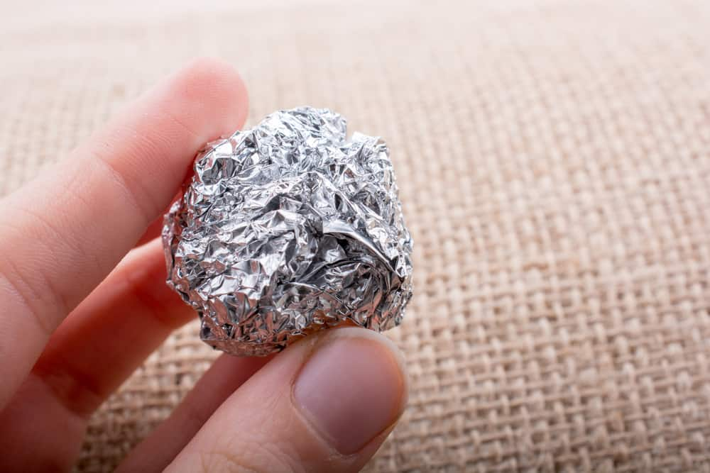 Aluminium foil in the shape of a sphere on a textured background