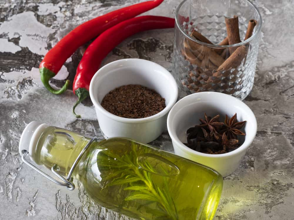 Spices (cinnamon, chili pepper, flax seeds, star anise, olive oil infused with rosemary) on the table