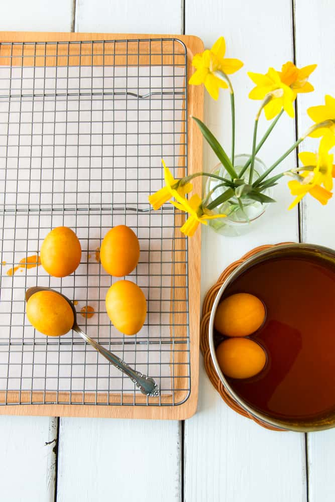 Dyeing Easter eggs natural way with turmeric for mustard - yellow color. Selective focus.