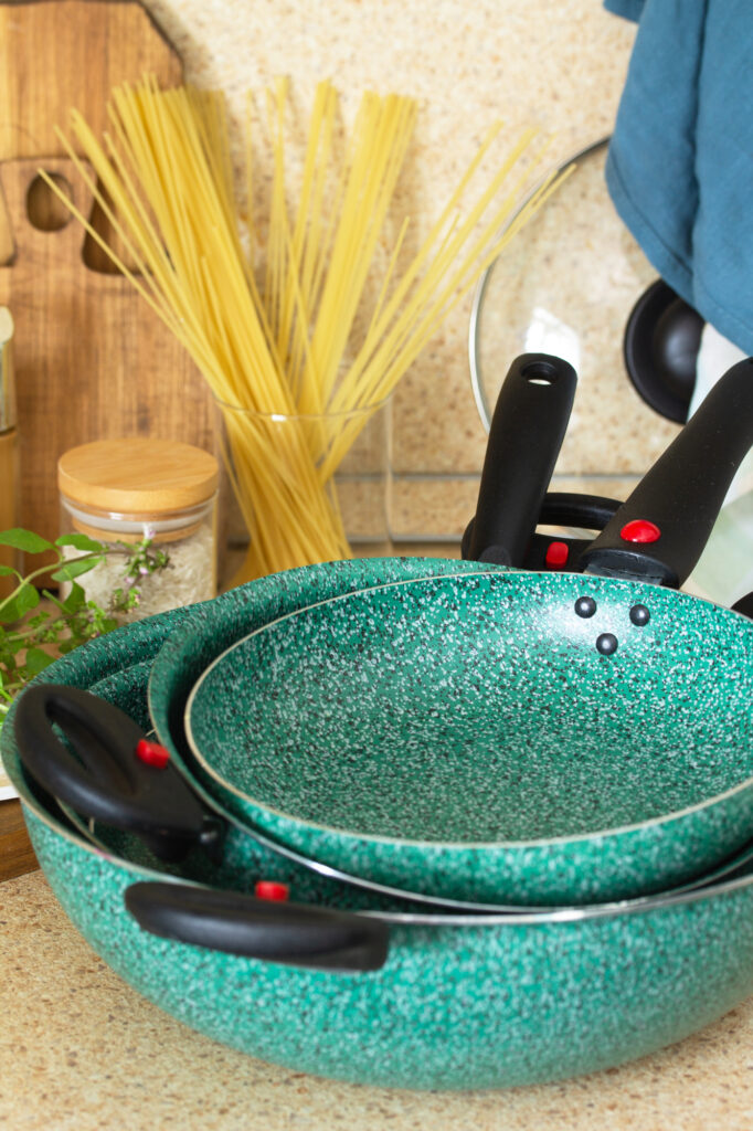 Set of empty ceramic coated dishes on a stone kitchen worktop surrounded. Kitchen table surrounded by Italian cuisine ingredients and frying pan.
