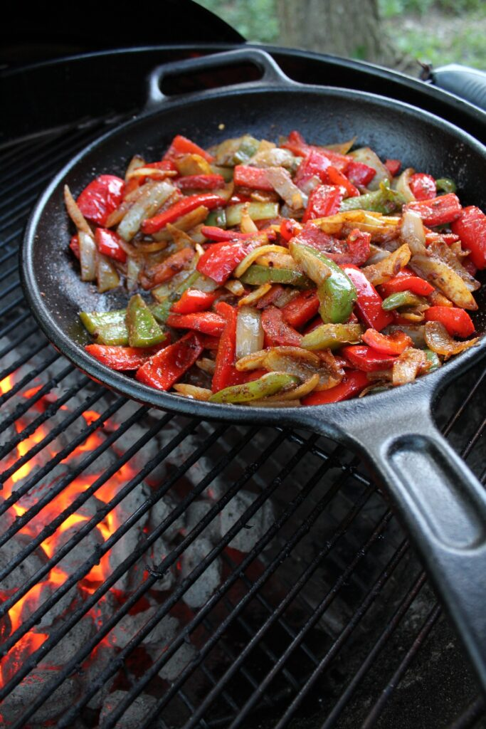 peppers onions and beef cooking in cast iron on grill