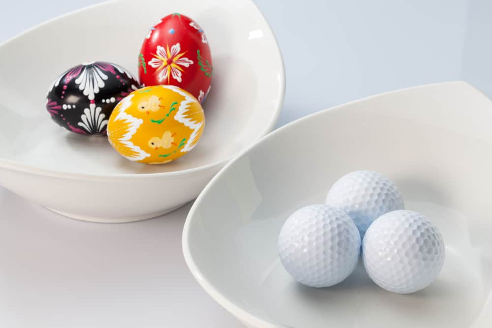 Two white ceramics bowls,golf balls and easter eggs