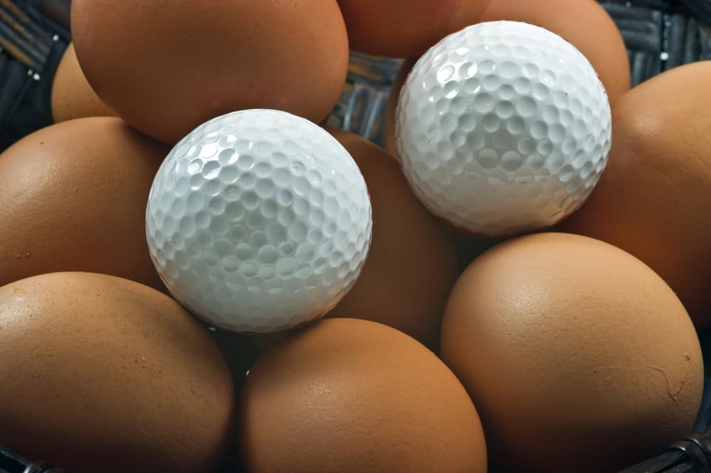 Golf balls with eggs in a basket